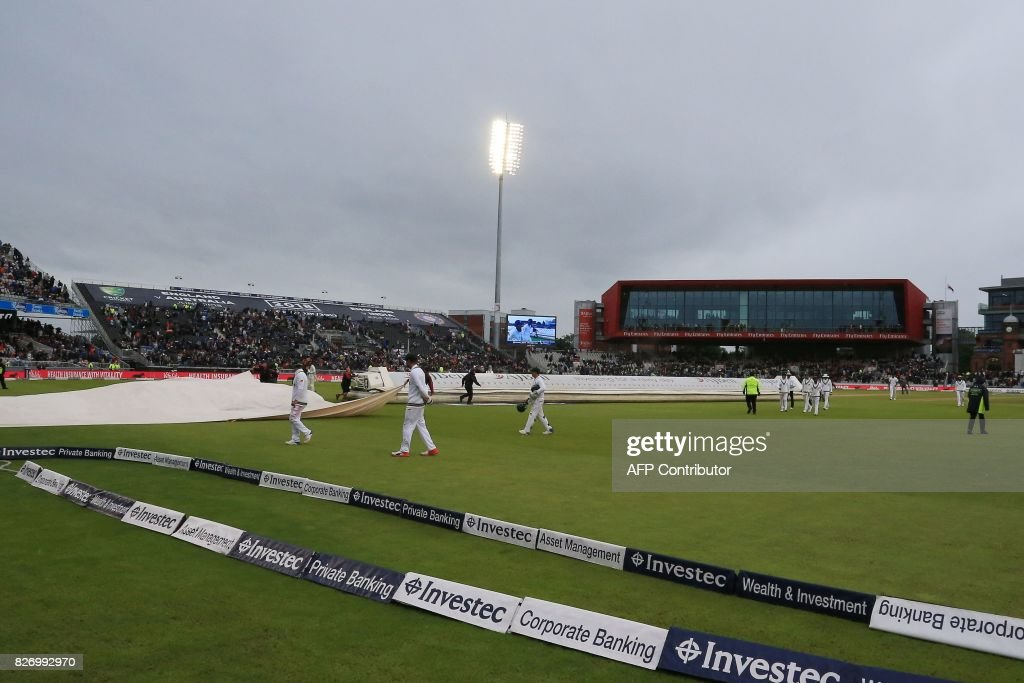 Players leave the pitch as rain stops play on day 3 of the fourth Test match between England and South Africa at Old Trafford cricket ground in Manchester on August 6, 2017. / AFP PHOTO / Lindsey Parnaby / RESTRICTED