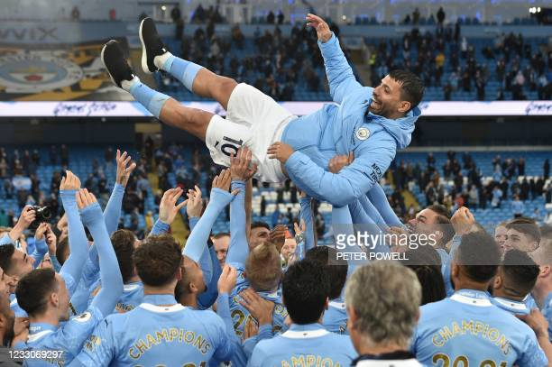 Players lifter Manchester City's Argentinian striker Sergio Aguero aloft during the trophy award ceremony after the English Premier League football...