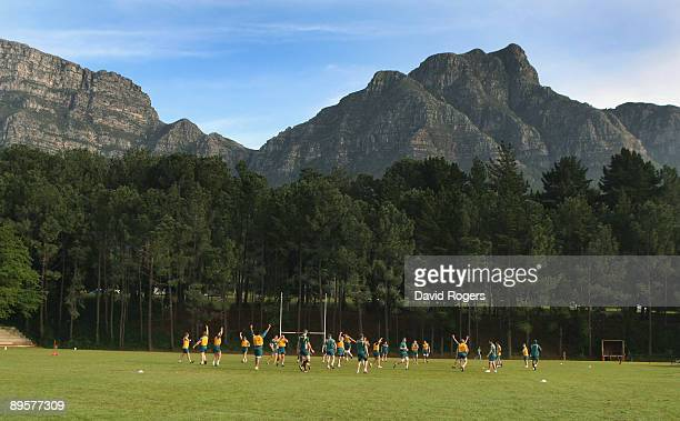 Players limber up overlooked by Table Mountain during the Australian Wallabies training session held at Westerford High School on August 3 2009 in...