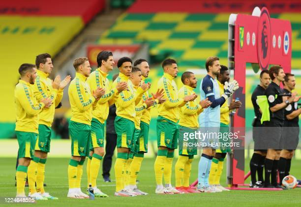 Players line up for a minute's applause to thank Britain's NHS workers ahead of the English Premier League football match between Norwich City and...
