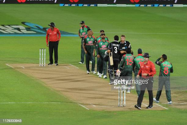 Players line up to shake hands following Game 1 of the One Day International series between New Zealand v Bangladesh at McLean Park on February 13...