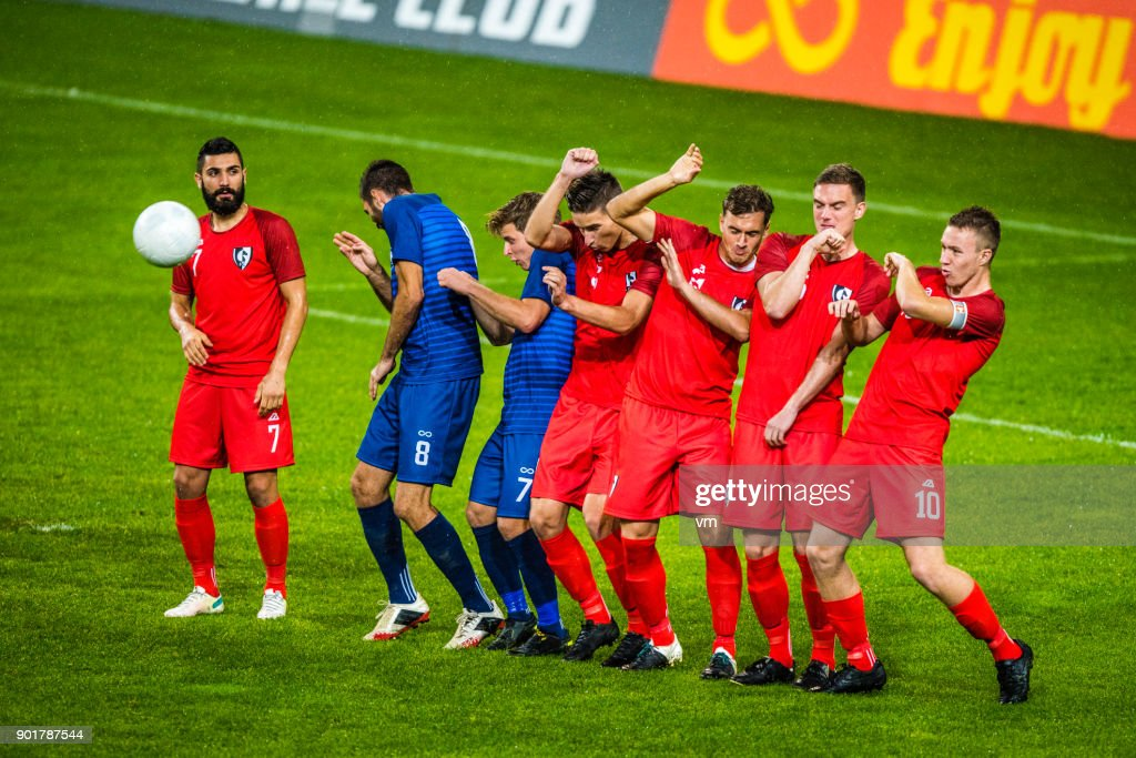 Players lined up defending from a free kick : Stock Photo