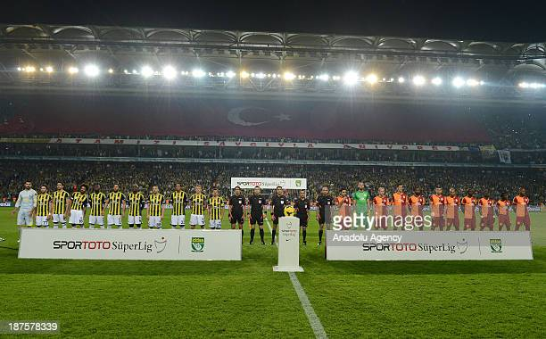 Players listen to national anthem prior to the Turkish Spor Toto Super League football match between Fenerbahce and Galatasaray at Sukru Saracoglu...