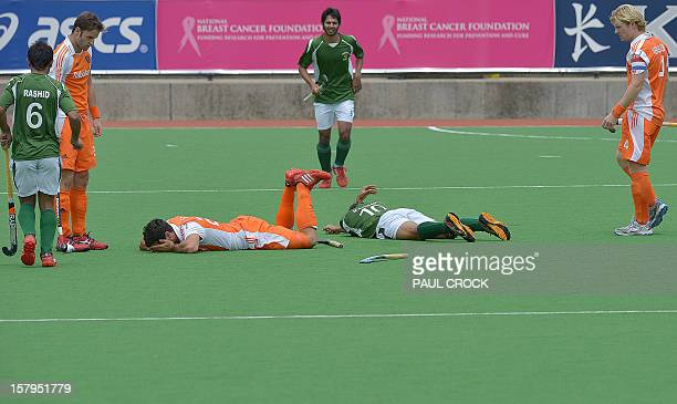 Players look on as Muhammad Rizwan Snr of Pakistan and Valentin Verga of the Netherlands lie on the pitch after clashing heads during their semifinal...