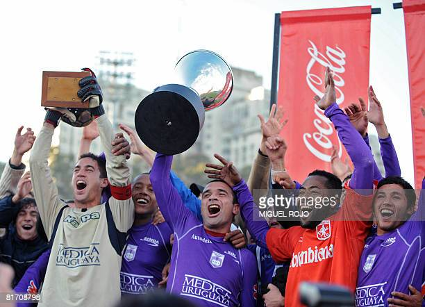 Players Martin Silva Pablo Gaglianone and Jairo Castillo of Defensor Sporting celebrate with the Cup after drawing 00 with Penarol in their Uruguayan...