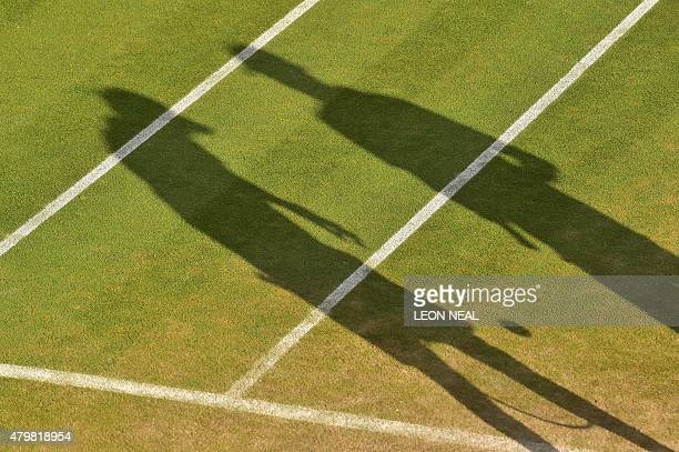 US players Mike Bryan and Bob Bryan's shadows are cast long on the court as they talk between points against India's Rohan Bopanna and Romania's...