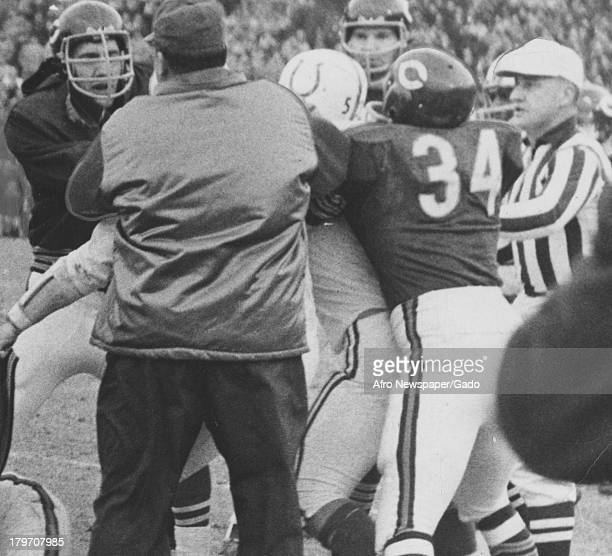 Players number 34 and 5 engage with teammates and officials in an unofficial scrimmage in 5star football game 1968