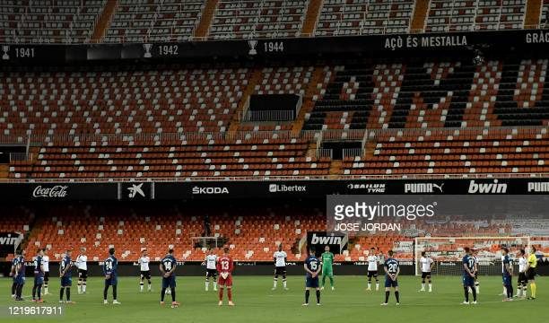 Players observe a minute of silence for the novel coronavirus victims before the Spanish League football match between Valencia and Levante at the...