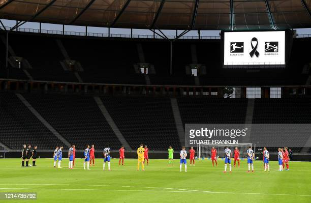 Players observe a minute of silence to commemorate the victims of the coronavirus pandemic prior to the German first division Bundesliga football...
