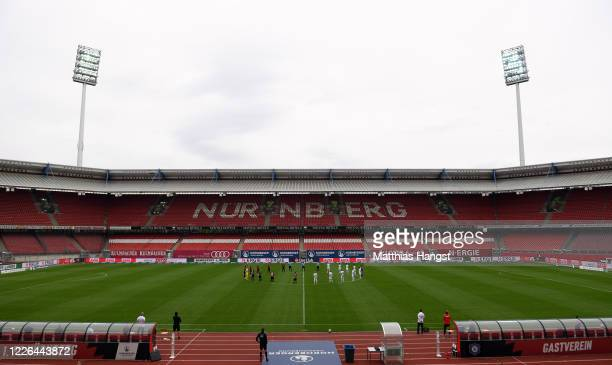 Players observe a minute's silence to commemorate the victims of the coronavirus pandemic prior to the Second Bundesliga match between 1. FC Nürnberg...