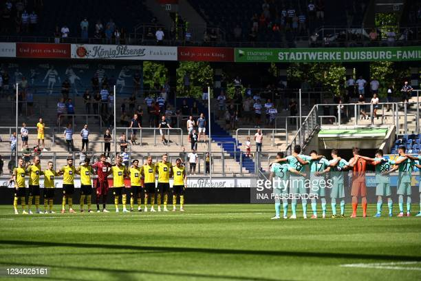 Players observe a moment of silence in memory of the victims of the floods prior to the start of the friendly football match Borussia Dortmund and...