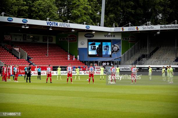 Players of 1. FC Heidenheim 1846 and SV Wehen Wiesbaden observe a minute of silence to commemorate the victims of the Corona pandemic prior to the...