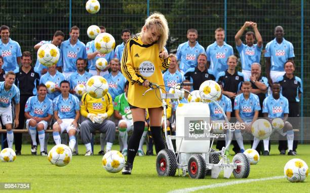 Players of 1860 Muenchen make fun with a model during the official team presentation on August 18, 2009 in Munich, Germany.
