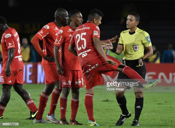 Players of America de Cali argue with referee Bismark Santiago during the second leg match between Millonarios and America de Cali as part of the...