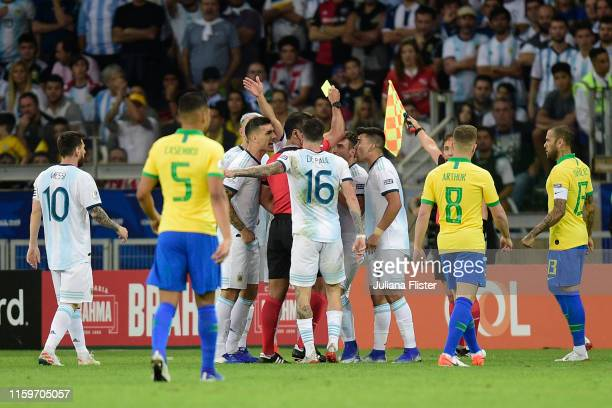 Players of Argentina argue with Referee Roddy Zambrano as he shows a yellow card to Nicolas Tagliafico of Argentina during the Copa America Brazil...