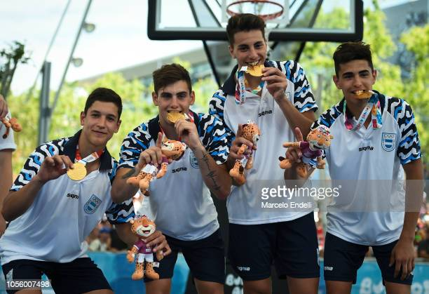 Players of Argentina bite their Gold medals after the Men's Gold Medal Game against Belgium during day 11 of he Buenos Aires Youth Olympic Games at...