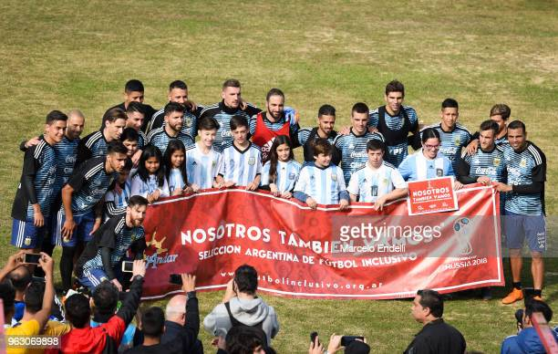 Players of Argentina pose with fans as they display a flag that reads 'We are also going' during a training session open to the public as part of the...