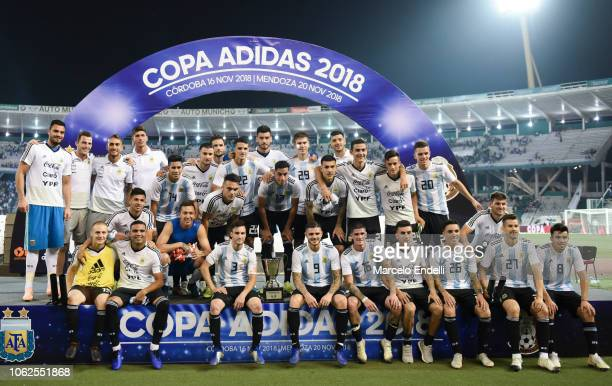 Players of Argentina pose with the Adidas Trophy after winning a friendly match between Argentina and Mexico at Mario Kempes Stadium on November 16...