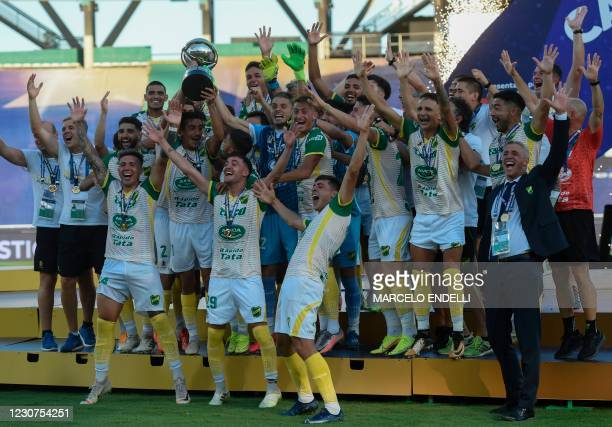 Players of Argentina's Defensa y Justicia celebrate on the podium with the trophy after winning the Copa Sudamericana final football match by...