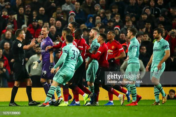 Players of Arsenal and Manchester United surround Referee Andre Mariner during the Premier League match between Manchester United and Arsenal FC at...