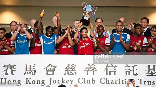 Players of Arsenal FC celebrate with trophy at the end of the pre-season Asian Tour friendly match between Kitchee FC and Arsenal at Hong Kong...