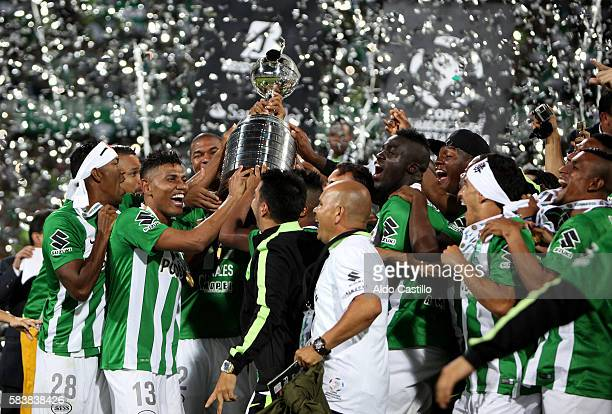 Players of Atletico Nacional celebrate with the trophy after a second leg final match between Atletico Nacional and Independiente del Valle as part...