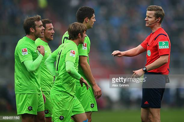 Players of Aue discuss with referee Arne Aarnink during the Second Bundesliga match between Karlsruher SC and Erzgebirge Aue at Wildpark Stadium on...