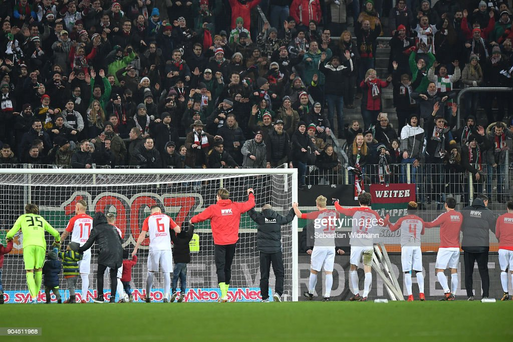 Players of Augsburg celebrate with their supporters after the Bundesliga match between FC Augsburg and Hamburger SV at WWK-Arena on January 13, 2018 in Augsburg, Germany.