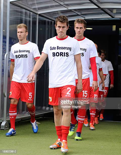 Players of Augsburg enter the pitch with a shirt for Boris Vukcevic for warm up prior to during the Bundesliga match between TSG 1899 Hoffenheim and...
