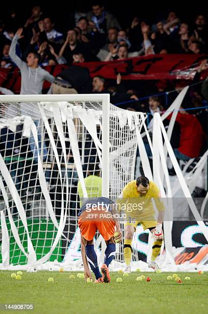 Players of Auxerre and Montpellier pick up tennis balls as Auxerre's supporters throw tennis balls and toilet paper on the pitch during the French L1...