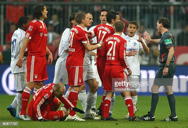 Players of Bayern Muenchen and Schalke argue with referee Florian Meyer after Arjen Robben was fouled during the Bundesliga match between FC Bayern...