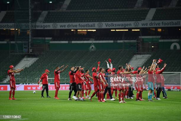 Players of Bayern Munich celebrate securing the Bundesliga title in front of empty stands following their victory in the Bundesliga match between SV...