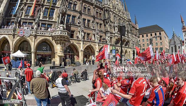 Players of Bayern Munich stand on the balcony of Munich's city hall as they celebrate with their fans winning the trophies of the German Cup and the...