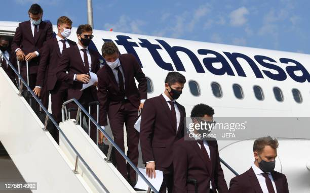 Players of Bayern Munich walk off the team plane as the Bayern Munich team arrive in Budapest ahead of the UEFA Super Cup Final between Sevilla and...