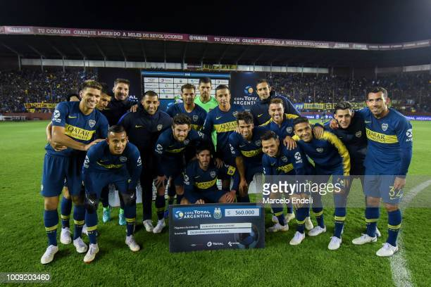 Players of Boca Juniors pose with the check to classify to Round of 32 after winning a match between Boca Juniors and Alvarado as part of Round of 64...