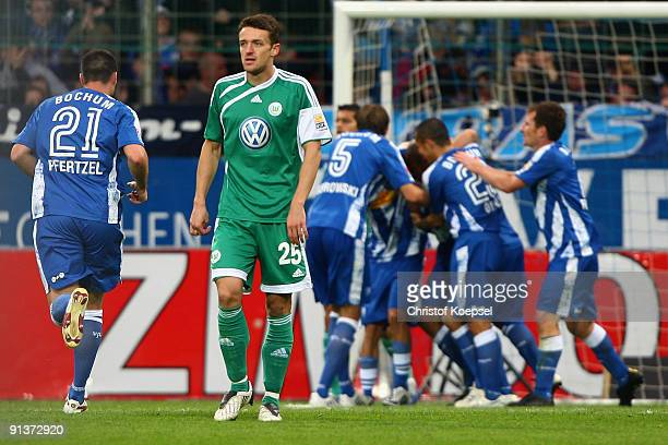 Players of Bochum celebrate their team's first goal and Christian Gentner of Wolfsburg looks dejected during the Bundesliga match between VFL Bochum...