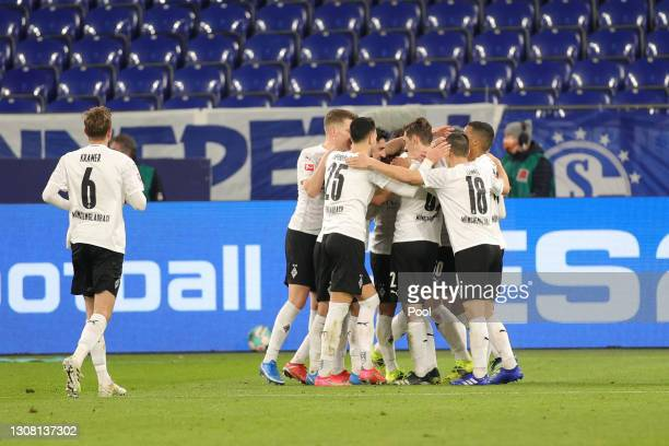 Players of Borussia Moenchengladbach celebrate their side's third goal which was an own goal scored by Frederik Ronnow of FC Schalke 04 during the...