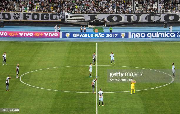 Players of Botafogo and Gremio observe a minutes' silence to pay tribute for AFP photographer Vanderlei Almeida who died last week after a long...