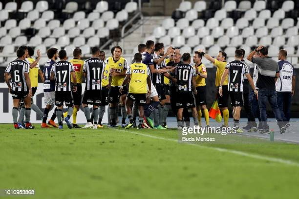 Players of Botafogo argue with assistant referee Pedro Martinelli Christino during a match between Botafogo and Santos as part of Brasileirao Series...