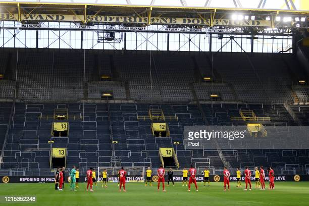 Players of both teams participate in a minute's silence to commemorate the victims of the Covid-19 pandemic prior to the Bundesliga match between...