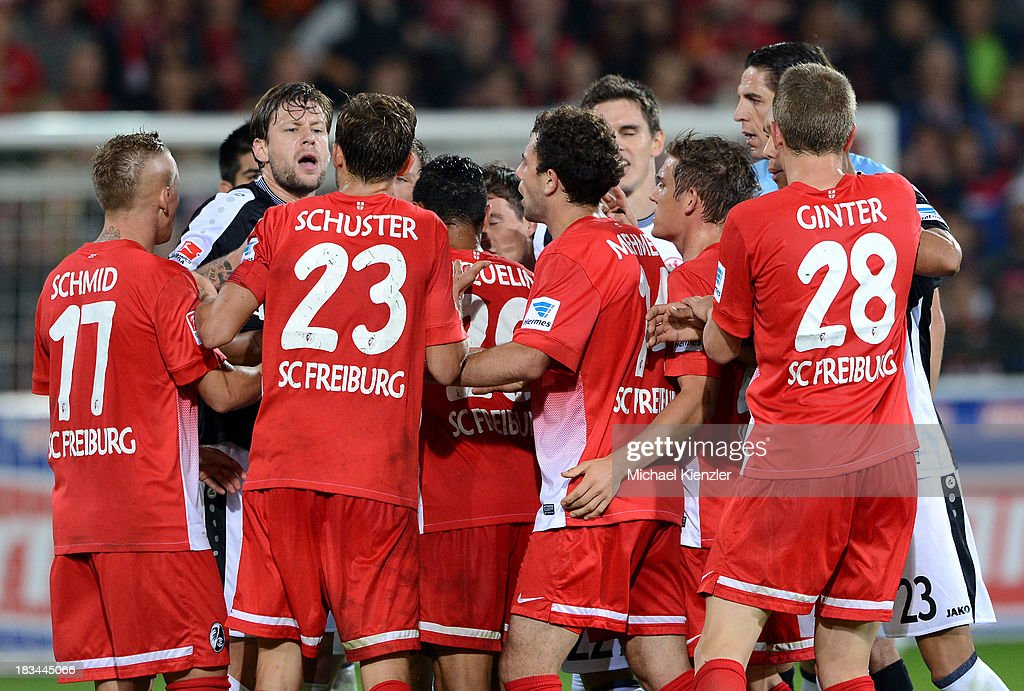 Players of both teams remonstrate after Johannes Flum of Frankfurt was shown a red card during the Bundesliga match between SC Freiburg and Eintracht Frankfurt at Mage Solar Stadium on October 6, 2013 in Freiburg, Germany.