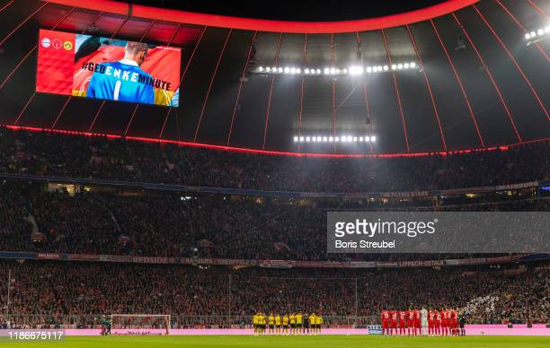 Players of both team's stand for a minute of silence for Robert Enke prior to the Bundesliga match between FC Bayern Muenchen and Borussia Dortmund...