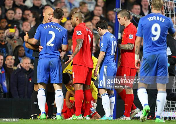 Players of botn teams including Branislav Ivanovic of Chelsea and Glen Johnson of Liverpool speak to Referee Howard Webb as Steven Gerrard of...