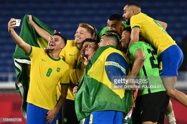 Players of Brazil pose for a selfie as they celebrate after winning the Tokyo 2020 Olympic Games football competition men's gold medal match by...