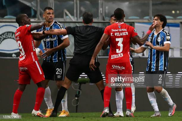Players of Brazil's Gremio and Colombia's America de Cali argue as Argentine referee Fernando Rapallini tries to control the situation during the...