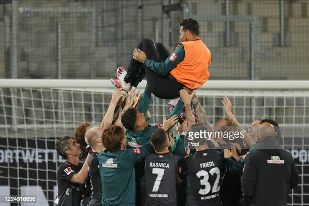 Players of Bremen toss teammate Claudio Pizarro in the air as they celebrate after the Bundesliga playoff second leg match between 1 FC Heidenheim...