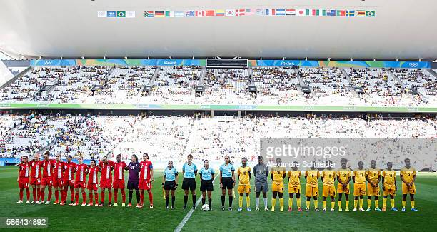 Players of Canada and Zimbabwe stand for the national anthen before the match between Canada and Zimbabwe womens football for the summer olympics at...
