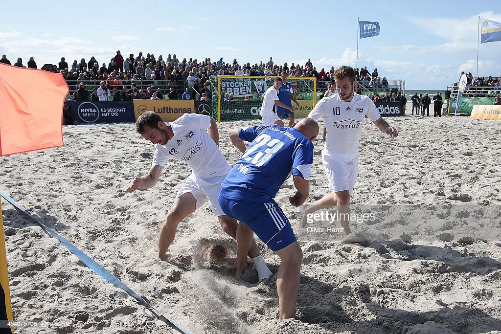 Players of Chemnitz (L) challenges a player of Rostock (C) during the final match between BST Chemnitz and Rostocker Robben on day two of the DFB Beachscoccer Cup at the beach of Warnemunde on August 24, 2014 in Warnemunde, Germany.