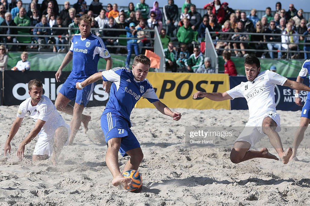 Players of Chemnitz (R) challenges a player of Rostock (L) during the final match between BST Chemnitz and Rostocker Robben on day two of the DFB Beachscoccer Cup at the beach of Warnemunde on August 24, 2014 in Warnemunde, Germany.