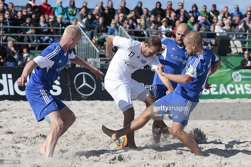 Players of Chemnitz (C) challenges a player of Rostock (R) during the final match between BST Chemnitz and Rostocker Robben on day one of the DFB Beachscoccer Cup at the beach of Warnemunde on August 24, 2014 in Warnemunde, Germany.